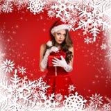 Muchacha de Papá Noel en el fondo rojo con los copos de nieve Fotografía de archivo