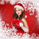 Muchacha de Papá Noel en el fondo rojo con los copos de nieve Imagenes de archivo