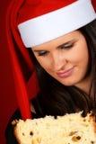 Muchacha de Papá Noel que come el panettone Foto de archivo libre de regalías