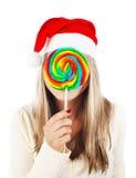 Muchacha de Papá Noel que come la piruleta Foto de archivo