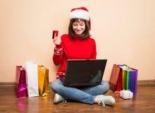 Muchacha de Papá Noel que compra en línea para la Navidad que se sienta en el piso con Fotografía de archivo
