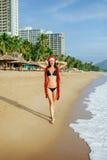 Muchacha de Papá Noel que hace deseo en la playa en las zonas tropicales Imagenes de archivo