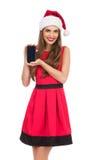 Muchacha de Papá Noel que presenta el teléfono móvil Imagen de archivo