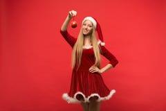 Muchacha de Papá Noel que presenta en un fondo rojo con el juguete Imagenes de archivo