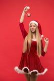 Muchacha de Papá Noel que presenta en un fondo rojo con el juguete Imágenes de archivo libres de regalías