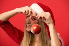 Muchacha de Papá Noel que presenta en un fondo rojo con el juguete Fotografía de archivo libre de regalías