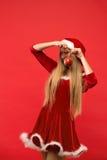 Muchacha de Papá Noel que presenta en un fondo rojo con el juguete Fotografía de archivo