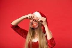 Muchacha de Papá Noel que presenta en un fondo rojo con el juguete Fotos de archivo libres de regalías