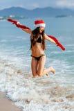 Muchacha de Papá Noel que salta en el mar en la playa Imagen de archivo