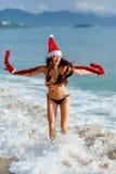 Muchacha de Papá Noel que salta en el mar en la playa Imagenes de archivo