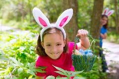 Muchacha de Pascua con la cesta de los huevos y la cara divertida del conejito Imagen de archivo