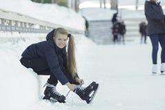 Muchacha de pelo largo adolescente que se sienta en la nieve que aprieta los cordones en los patines y la sonrisa Foto de archivo libre de regalías