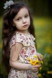 Muchacha de pelo largo con las flores amarillas Fotos de archivo libres de regalías