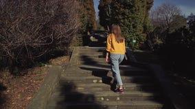 Muchacha de pelo largo en subidas casuales las escaleras de piedra en el jardín almacen de metraje de vídeo