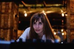 Muchacha de pelo largo en una blusa blanca la muchacha mira para arriba, vida nocturna, partido imagenes de archivo