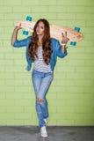 Muchacha de pelo largo hermosa con un longbord de madera cerca de un b verde Fotos de archivo libres de regalías