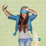 Muchacha de pelo largo hermosa con un smartphone cerca de un ladrillo verde Imagenes de archivo