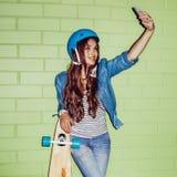 Muchacha de pelo largo hermosa con un smartpnone cerca de un ladrillo verde Fotografía de archivo libre de regalías