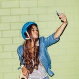 Muchacha de pelo largo hermosa con un smartpnone cerca de un ladrillo verde Imagenes de archivo