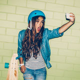 Muchacha de pelo largo hermosa con un smartpnone cerca de un ladrillo verde Foto de archivo