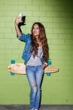 Muchacha de pelo largo hermosa con un teléfono móvil cerca de un ladrillo verde w Imágenes de archivo libres de regalías