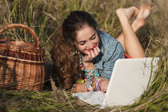 Muchacha de pelo largo que miente en el ordenador portátil y la sonrisa Imagen de archivo libre de regalías