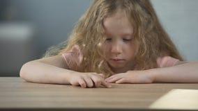 Muchacha de pelo largo resentida que se sienta en la tabla y que piensa en propio comportamiento almacen de video