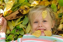 Muchacha de pelo rubio que miente en las hojas de otoño imagenes de archivo