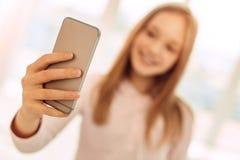 Muchacha de pelo rubio que sostiene el teléfono y que toma el selfie Imagenes de archivo