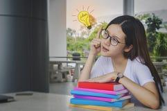 Muchacha de pensamiento del estudiante de la idea con los vidrios y los libros en el escritorio, agujereado Imagen de archivo