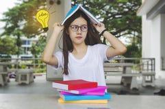 Muchacha de pensamiento del estudiante de la idea con los vidrios y los libros en el escritorio, agujereado Imagenes de archivo