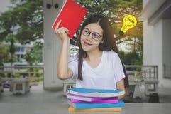 Muchacha de pensamiento del estudiante de la idea con los vidrios y los libros en el escritorio, agujereado Fotografía de archivo