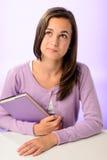 Muchacha de pensamiento del estudiante que se sienta detrás de púrpura del escritorio Foto de archivo