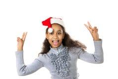 Muchacha de piel morena alegre en una bufanda y un sombrero rojos de Santa Claus Imagenes de archivo