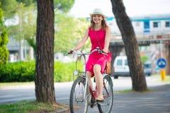 Muchacha de Preaty en el sombrero y el vestido rosado que montan una bicicleta Imagenes de archivo