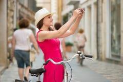 Muchacha de Preaty en el sombrero y el vestido rosado que montan una bicicleta Imagen de archivo