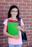 Muchacha de Preteenager al lado de una pared de ladrillo roja con la mochila y Foto de archivo libre de regalías