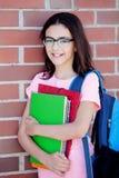 Muchacha de Preteenager al lado de una pared de ladrillo roja con la mochila y Imagen de archivo