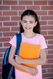 Muchacha de Preteenager al lado de una pared de ladrillo roja con la mochila y Fotos de archivo