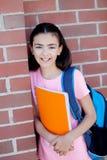 Muchacha de Preteenager al lado de una pared de ladrillo roja con la mochila y Fotografía de archivo
