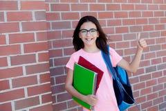 Muchacha de Preteenager al lado de una pared de ladrillo roja con la mochila y Fotografía de archivo libre de regalías
