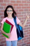 Muchacha de Preteenager al lado de una pared de ladrillo roja con la mochila y Fotos de archivo libres de regalías