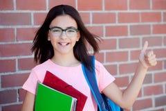 Muchacha de Preteenager al lado de una pared de ladrillo roja con la mochila y Foto de archivo