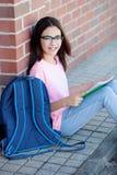 Muchacha de Preteenager con la mochila que se sienta en el piso Imágenes de archivo libres de regalías