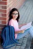 Muchacha de Preteenager con la mochila que se sienta en el piso Imagen de archivo libre de regalías