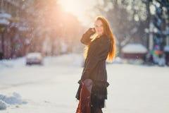 Muchacha de Redhair en invierno en la puesta del sol Imagenes de archivo