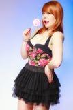 Muchacha de Redhair que sostiene el caramelo dulce de la piruleta de la comida en azul Fotos de archivo libres de regalías