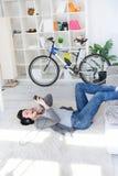 Muchacha de relajación que miente en suelo en sala de estar Imagenes de archivo