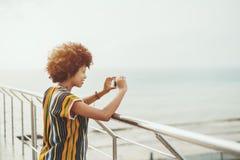 Muchacha de risa afroamericana que toma la imagen en el teléfono Fotografía de archivo libre de regalías