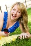 Muchacha de risa con un teléfono celular Fotos de archivo
